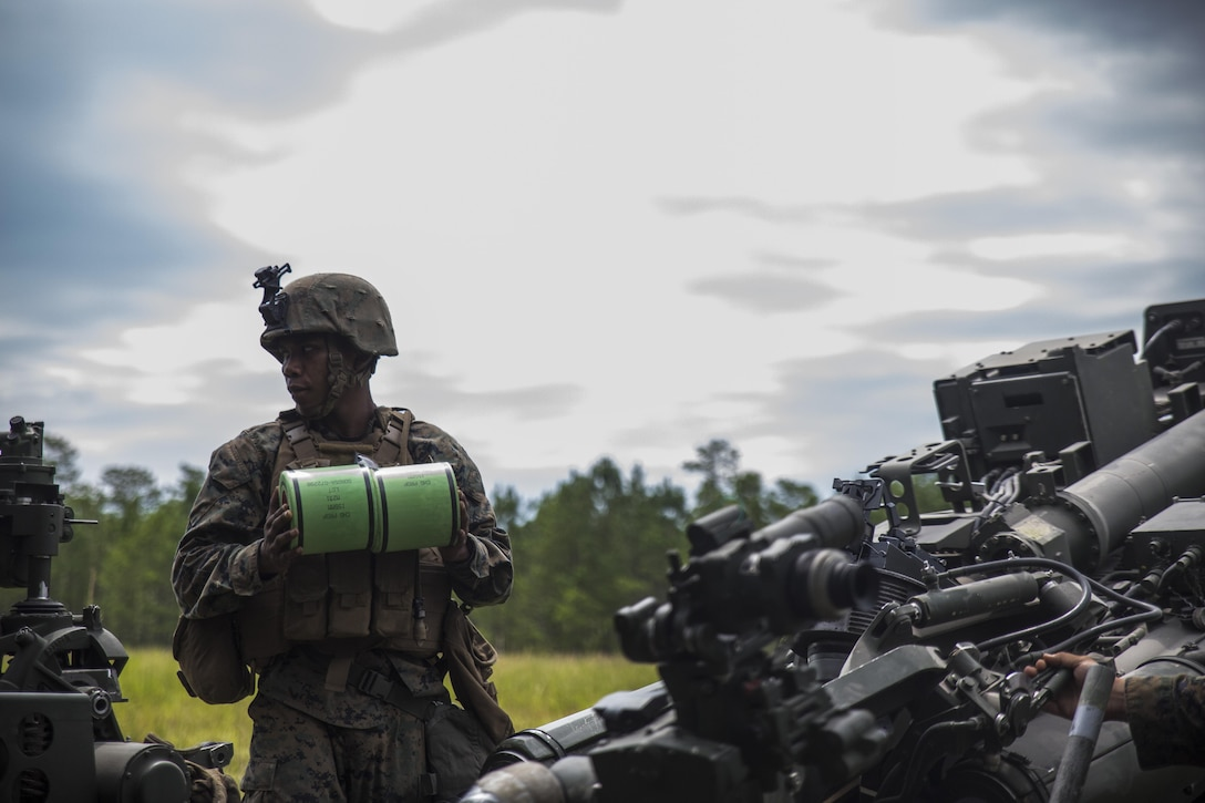 A Marine prepares to load the charge into an M777A2 Howitzer during a live-fire range at Camp Lejeune, N.C., July 26, 2017. The purpose of this field operation is to test and improve the unit's capabilities by putting the Marines into a simulated combat environment. The Marine is with 1st Battalion, 10th Marine Regiment. (U.S. Marine Corps photo by Lance Cpl. Holly Pernell)
