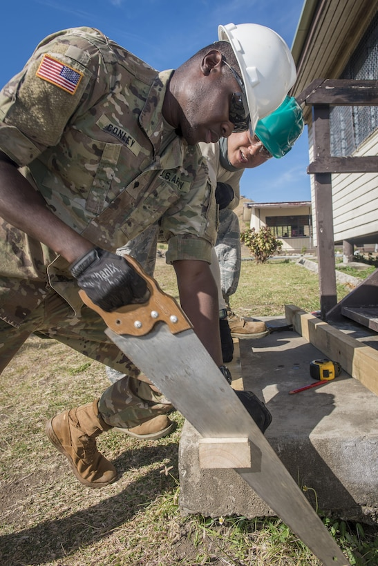U.S. Army Spc. Solomon Conley, a carpentry and masonry specialist with the 523rd Engineer Company at Schofield Barracks, Hawaii, cuts a board to length as U.S. Air Force Staff Sgt. Kyle Quinata, a structural engineer with the 254th Red Horse Squadron at Andersen Air Force Base, Guam, observes during Pacific Angel (PACANGEL) 17-3 at Karave Primary School in Ba, Fiji, July 18, 2017. Conley and Quinata worked together to rebuild steps to a schoolhouse while others on their engineering team reconstructed roofing supports and new plumbing installed. Service members from more than five nations joined the U.S. to work together to rebuild certain areas of Fiji during PACANGEL 17-3. (U.S. Air Force photo/Tech. Sgt. Benjamin W. Stratton)
