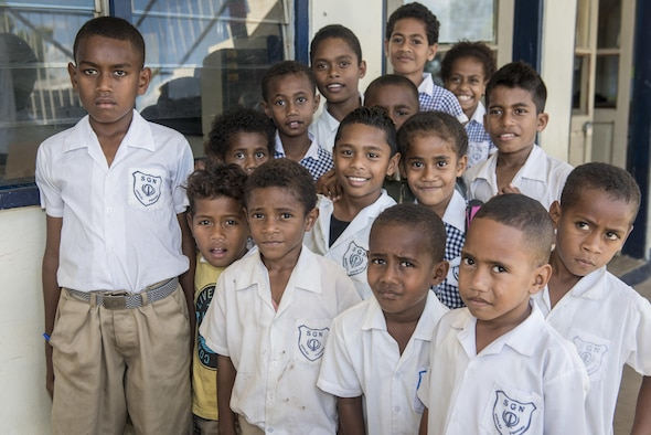 A group of Fijian students pose for the camera at Khalsa Primary School during Pacific Angel (PACANGEL) 17-3 in Ba, Fiji, July 18, 2017. The kids were joined by several U.S. and Fijian engineers working together to install new and renovate existing infrastructure such as ceiling fans and water piping. PACANGEL builds partnerships between the US, Fiji, and several regional nations by conducting multilateral humanitarian assistance and civil military operations, promoting regional military-civilian-nongovernmental organization cooperation and interoperability. (U.S. Air Force photo/Tech. Sgt. Benjamin W. Stratton)