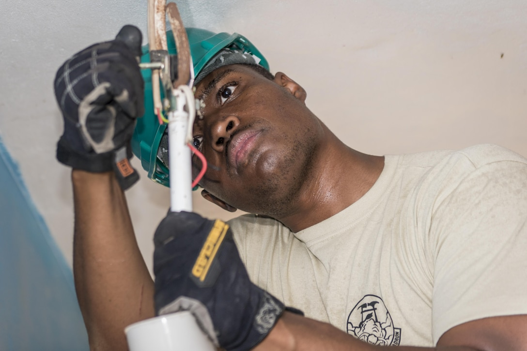 U.S. Air Force Staff Sgt. Quintin Robinson, an electrician with the 374th Civil Engineer Squadron at Yokota Air Base, Japan, rewires a ceiling fan at Khalsa Primary School during Pacific Angel (PACANGEL) 17-3 in Ba, Fiji, July 18, 2017. Robinson joined two U.S. Air Force water and fuels specialists and their Fijian counterparts in Ba, working hand-in-hand to ensure the children and their teachers could have operable ceiling fans and running water. PACANGEL 17-3 strengthens participating armed forces and nongovernmental organizations interoperability so they can be ready in the event of an unforeseen natural disaster such as the cyclone that hit Fiji in 2015. (U.S. Air Force photo/Tech. Sgt. Benjamin W. Stratton)