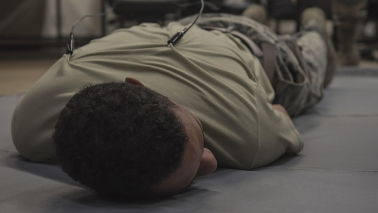 U.S. Air Force Airman 1st Class Jamsen Hayden, 18th Security Forces Squadron defender, lays down for a demonstration of the 'ride the lightning' during Taser and oleoresin capsicum (OC)  spray training July 20, 2017, at Kadena Air Base, Japan. Defenders were able to choose what position they preferred to be in for this portion, including laying down, or having the clips attached to their abdomen, calves, or standing up. (U.S. Air Force photo/ Airman 1st Class Greg Erwin)