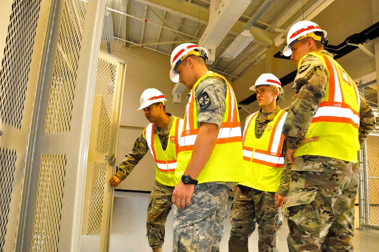 Capt. Rodolfo Martinez (far left) a project engineer, inspects a wall locker and explains deficiencies to Cadet Drako Gagnon (left) University of Winsconsin-River Falls, Cadet Tim Gephart (center)  United States Military Academy, and Cadet Caleb Kowalski University of Winsconsin-Madison, during a site walk on July 27, 2017.