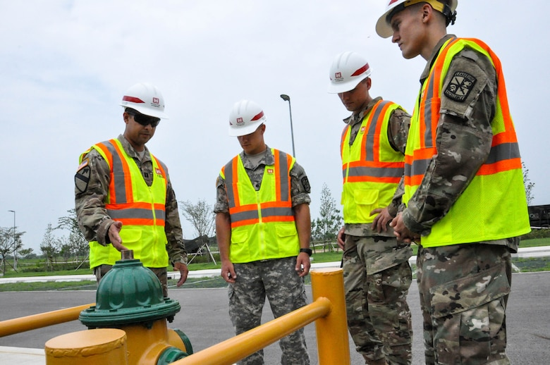 Capt. Rodolfo Martinez (left) a project engineer, explains a fire extinguisher modification to Cadet Caleb Kowalski (left), University of Winsconsin-Madison, Cadet Tim Gephart (center) United States Military Academy, and Cadet Drako Gagnon, University of Winsconsin-River Falls, during a site walk on July 27, 2017.