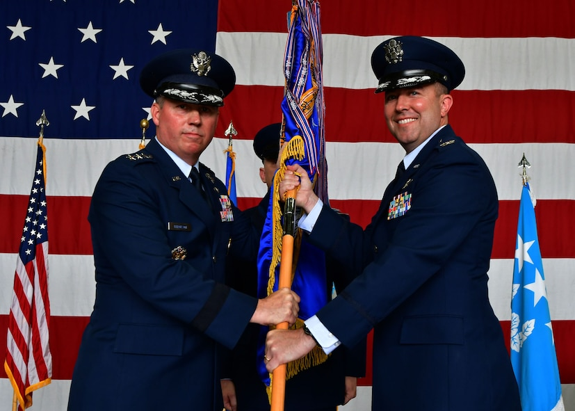 """U.S. Air Force Lt. Gen. Thomas Bergeson, 7th Air Force commander, passes the 51st Fighter Wing guidon to U.S. Air Force Col. William """"Wilbur"""" Betts, 51st FW incoming commander, during the 51st FW Change of Command Ceremony on July 27, 2017, at Osan Air Base, Republic of Korea. The ceremony consisted of U.S. Air Force Col. Andrew """"Popeye"""" Hansen relinquishing command of the 51st FW to U.S. Air Force Col. William """"Wilbur"""" Betts. The 51st FW provides combat ready forces for close air support, air strike control, forward air control-airborne, combat search and rescue, counter air and fire, and interdiction in defense of the ROK. (U.S. Air Force photo by Senior Airman Franklin R. Ramos/Released)"""