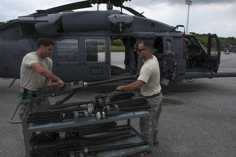 U.S. Air Force Staff Sgt. Ryan Anderson and Tech. Sgt. Josean Arce, 33rd Helicopter Maintenance Unit weapons section weapons technicians, ready a GAU-18 50-caliber machine gun to be loaded onto an HH-60 Pave Hawk from the 33rd Rescue Squadron July 26, 2017, at Kadena Air Base, Japan. When mounted to an HH-60 Pave Hawk, the weapons are manned by special mission aviators for real-world and training operations. (U.S. Air Force photo by Senior Airman John Linzmeier)