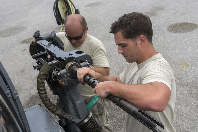 U.S. Air Force Senior Airman Zachary Hough and Staff Sgt. Ryan Anderson, 33rd Helicopter Maintenance Unit weapons section weapons load technicians, load a GAU-18 50-caliber machine gun onto an HH-60 Pave Hawk from the 33rd Rescue Squadron July 26, 2017, at Kadena Air Base, Japan. The GAU-18's mobile design allows it to be mounted on an HH-60 Pave Hawk and is capable of firing 650 to 750 rounds per-minute. (U.S. Air Force photo by Senior Airman John Linzmeier)