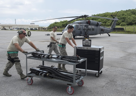 U.S. Air Force Senior Airman Zachary Hough, Tech. Sgt. Josean Arce and Staff Sgt. Ryan Anderson, 33rd Helicopter Maintenance Unit weapons section weapons load technicians, transport GAU-18 50-caliber machine gun toward an HH-60 Pave Hawk from the 33rd Rescue Squadron July 26, 2017, at Kadena Air Base, Japan. The weapons section provides defensive-counter-air lethality to nine HH-60 Pave Hawks from the 33rd Rescue Squadron. (U.S. Air Force photo by Senior Airman John Linzmeier)