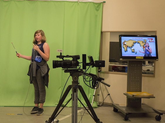 Olivia Forester, a Marine Corps Air Station Iwakuni resident, role-plays as a meteorologist during a trip with the Youth and Teen Center to Kidzania in Kobe, Japan, July 26, 2017. Kidzania is an indoor education entertainment center that provides children the interactive experience of working adult jobs and earning currency. Children are able to dress up and role-play as adults in nearly 100 jobs and activities with each profession offering the chance to use life-like tools and equipment. (U.S. Marine Corps photo by Lance Cpl. Carlos Jimenez)