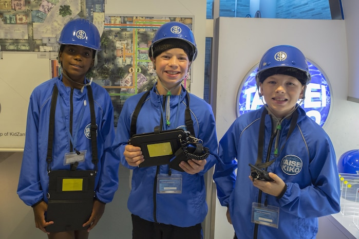 From left to right, Ciera Roberts, Parker Staley and Carter Staley, Marine Corps Air Station Iwakuni residents, dress up as waterworks service workers during a trip with the Youth and Teen Center to Kidzania in Kobe, Japan, July 26, 2017. Kidzania is an indoor education entertainment center that provides children the interactive experience of working adult jobs and earning currency. Children are able to dress up and role-play as adults in nearly 100 jobs and activities with each profession offering the chance to use life-like tools and equipment. (U.S. Marine Corps photo by Lance Cpl. Carlos Jimenez)