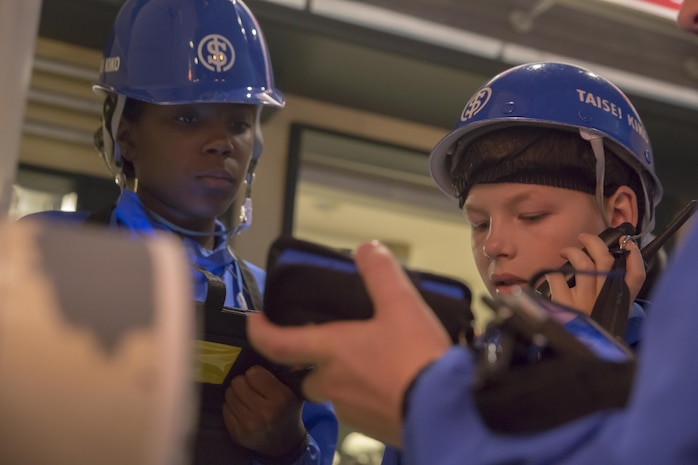 Ciera Roberts, left, and Carter Staley, Marine Corps Air Station Iwakuni residents, dress up as waterworks service workers during a trip with the Youth and Teen Center to Kidzania in Kobe, Japan, July 26, 2017. Kidzania is an indoor education entertainment center that provides children the interactive experience of working adult jobs and earning currency. Children are able to dress up and role-play as adults in nearly 100 jobs and activities with each profession offering the chance to use life-like tools and equipment. (U.S. Marine Corps photo by Lance Cpl. Carlos Jimenez)