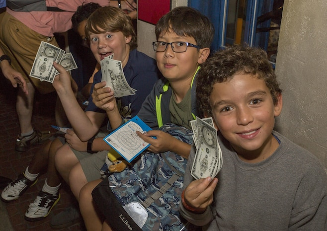 Youth and Teen Center members from Marine Corps Air Station Iwakuni hold up Kidzos, a special currency used in the theme park Kidzania in Kobe, Japan, July 26, 2017. Kidzania is an indoor education entertainment center that provides children the interactive experience of working adult jobs and earning currency. The currency can be spent on activities and used to buy souvenirs from gift shops. (U.S. Marine Corps photo by Lance Cpl. Carlos Jimenez)