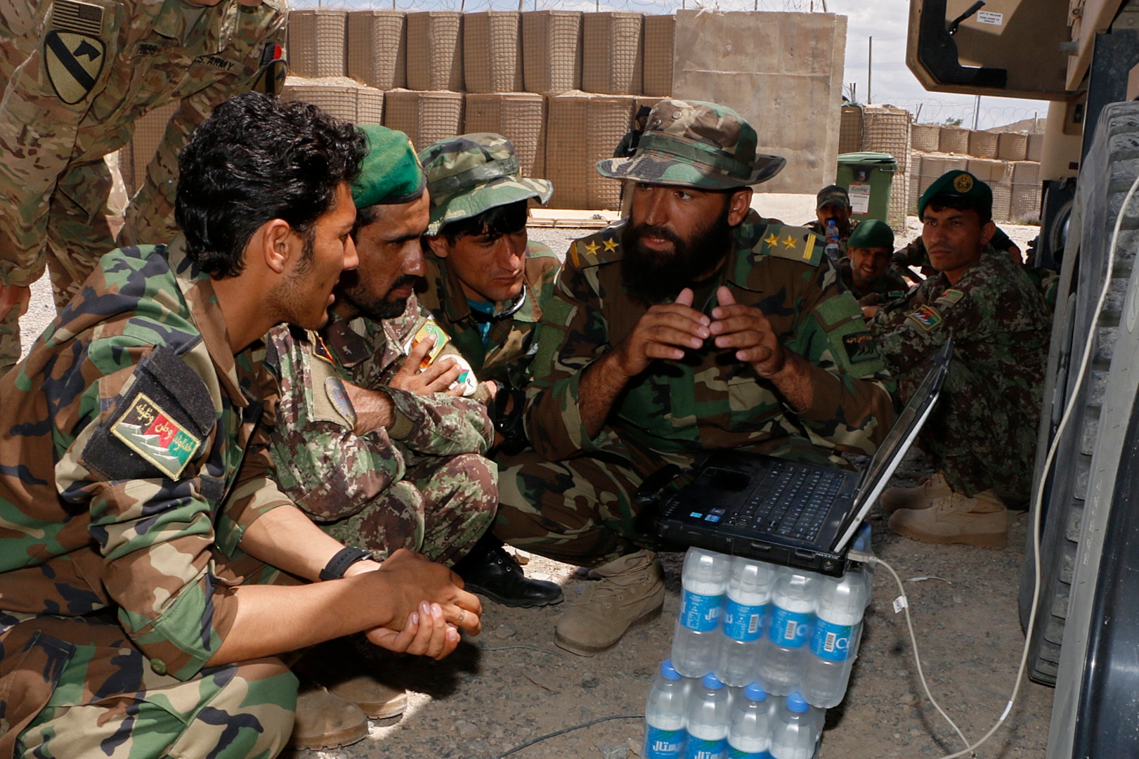 An Afghan National Army officer teaches ANA Soldiers about filling Electronic Warfare equipment under supervision of Staff Sgt. Justin Hood, Electronic Warfare Specialist for the Military Advisor Team of Task Force Southeast, during an Electronic Warfare training July 6 with Afghan National Army Soldiers of the 203rd Thunder Corps on AP Lightning. The purpose of the Train, Advise and Assist mission is to enable and develop the Afghan National Defense Security Forces with systems and processes that will continue to enable them into the future. (U.S. Army photo provided by Sgt. Christopher B. Dennis, 1st Cavalry Division PAO.)