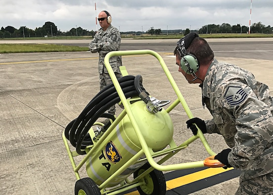 Master Sgt. Roger Carr, crew chief with the 507th Aircraft Maintenance Squadron at Tinker Air Force Base, Okla., moves a fire extinguisher across the flightline prior to a KC-135R Stratotanker refueling flight at RAF Mildenhall, England, as Senior Master Sgt. Justin Henry, 507th AMXS NCO in charge, looks on, July 25, 2017. In a long-standing partnership between the Air Force Reserve Command and U.S. Air Forces in Europe, members of the 507th Air Refueling Wing are augmenting the 100th Air Refueling Wing July 1-29, to provide KC-135R air refueling support to the European theater of operations. (U.S. Air Force photo/Tech Sgt. Lauren Gleason