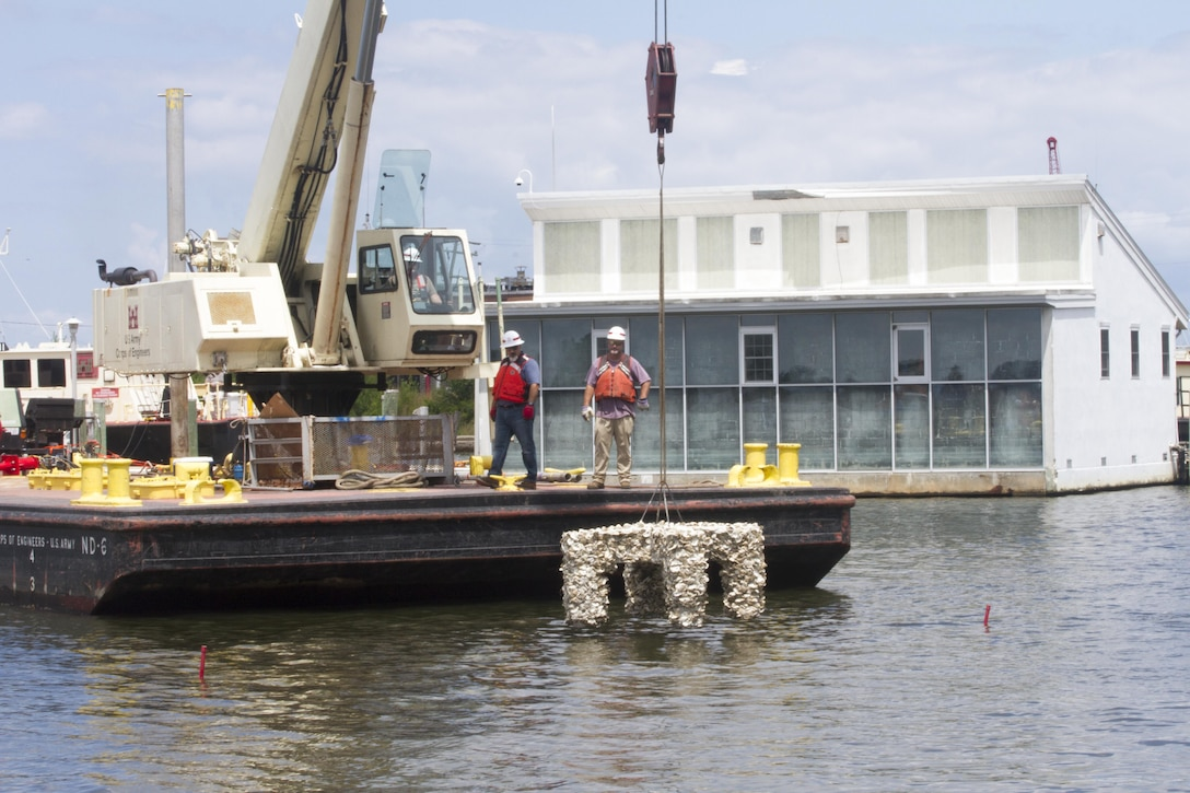 NORFOLK, Va. -- Employees from the Norfolk District use a crane barge to lower an oyster cross into the Elizabeth River at the district's headquarters building near downtown Norfolk on July 26, 2017. Three crosses were placed in the river and will serve as new habitat for oysters. (U.S. Army photo/Patrick Bloodgood)