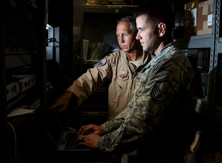 Master Sgt. Kyle Tschida, a Joint Interface Control cell watch officer with the 609th Air Operations Center, right, and Lt. Col. Terry Brennan, deputy U.S. Air Forces Central Command JIC officer, review datalink software changes July 21, 2017, at the Combined Air Operations Center on Al Udeid Air Base, Qatar. Brennan led a team that re-engineered theater data link architecture and provided reliable connectivity and responsive data link message traffic for the warfighter. (U.S. Air Force photo by Staff Sgt. Alexander Riedel)