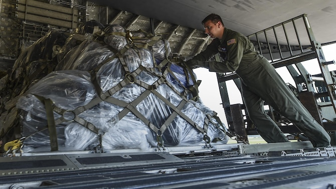 A loadmaster from the 15th Airlift Squadron at Joint Base Charleston, S.C. loads cargo onto a C-17 July 23, 2017, at Little Rock Air Force Base, Ark. Eight Little Rock C-130Js will travel alongside the C-17 aircrew to participate in Mobility Guardian 2017, a massive joint exercise at Joint Base Lewis-McChord, Wash. (U.S. Air Force photo by Staff Sgt. Harry Brexel)