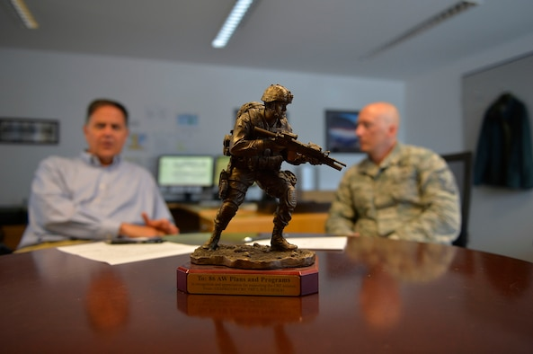 A trophy for the 86th Airlift Wing Plans and Programs Office stands in the middle of a table during a meeting on Ramstein Air Base, Germany, July 26, 2017. 86th AW XP integrates information and creates solutions concerning missions and operations coming in and out of Ramstein. The office acts as a liaison between incoming missions and the agencies they need to meet. (U.S. Air Force photo by Airman 1st Class Joshua Magbanua)