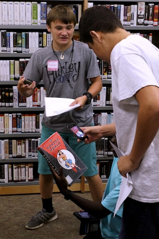 Craven County high school students participate in a scavenger hunt during a Stand Out Leaders in Training teen leadership day aboard Marine Corps Air Station Cherry Point, N.C., July 25, 2017. The young adults explored the Warrior library during a scavenger hunt that taught them what resources the library has to offer. The Cherry Point School Liaison Program hosted the event to actively engage local school-age children in leadership and team-building exercises aboard the installation. (U.S. Marine Corps photo by Cpl. Jason Jimenez/ Released)