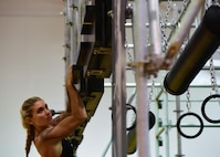 Brittany Reid, an Alpha Warrior professional, demonstrates how to complete the Alpha Warrior obstacle course at Whiteman Air Force Base, Mo., July 22, 2017. A permanent rig was set-up at the fitness center for the base populace to use and prepare for regionals.