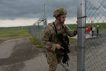 U.S. Air Force Senior Airman Andrew Delvo, of the 219th Security Forces Squadron, unlocks and opens the gate as he prepares to leave a missile alert facility in the Minot Air Force Base missile field complex, near Minot, N.D., June 15, 2017. He is a member of the North Dakota Air National Guard working seamlessly, side-by-side with U.S. Air Force active duty security forces members of the 91st Missile Wing as they maintain security standards in the missile fields. (U.S. Air National Guard Photo by Senior Master Sgt. David H. Lipp/Released)