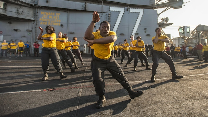 This image shows dancers performing on a ship's flight deck.