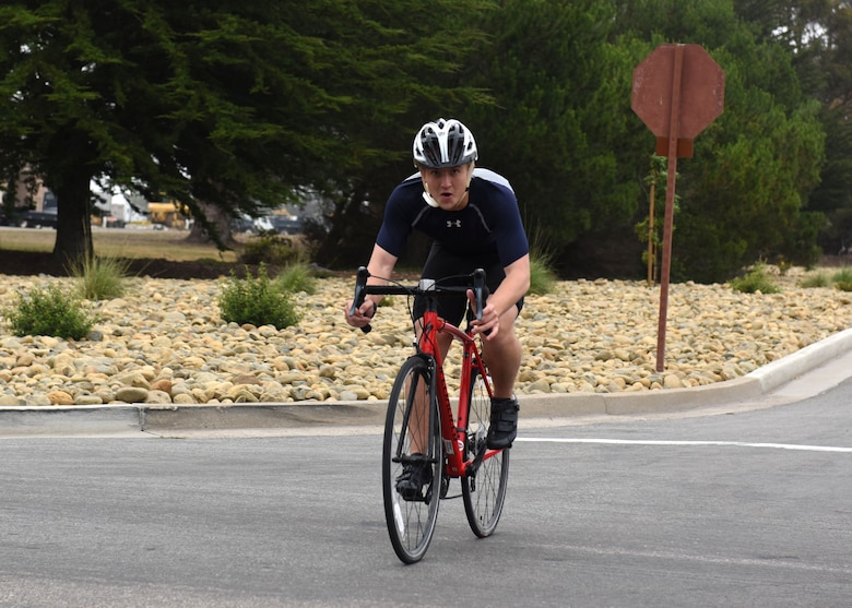 Airman 1st Class Clayton Wear, 30th Space Wing Public Affairs photojournalist, completes the bike portion of the base triathlon, July 22, 2017, Vandenberg Air Force Base, Calif. The base triathlon consisted of a 400-meter swim, a 20-kilometer bike, and a 5-kilometer run. (U.S. Air Force photo by Senior Airman Kyla Gifford/Released)