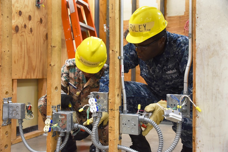 Major Ashrar Altarawneh and Seaman Devon Riley, 366th Training Squadron electrical systems apprentice course students install the duplex receptacle 120 volts switch at Sheppard Air Force Base, Texas. This course provides initial training for students to perform installation and maintenance duties of interior electrical systems. (U.S. Air Force photo/Liz H. Colunga)