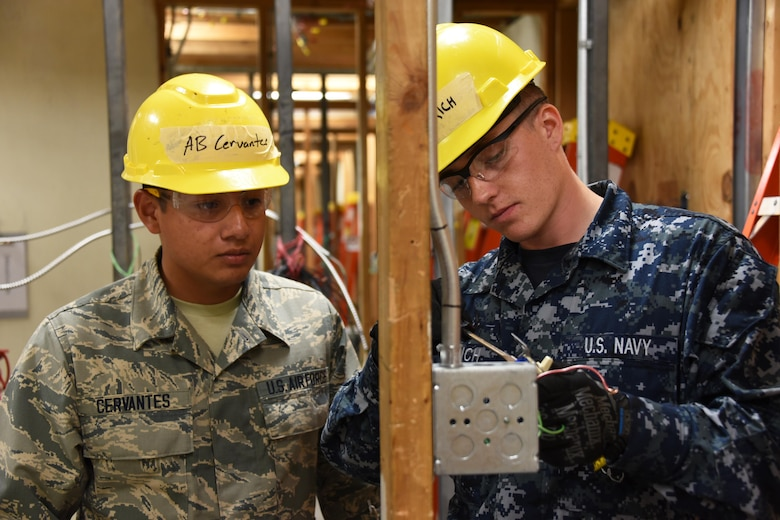 Airman Ángel Cervantes and Seaman William Dietrich, 366th Training Squadron electrical systems apprentice course students check the power on a three-way switch at Sheppard Air Force Base, Texas. This course provides initial training for students to perform installation and maintenance duties of interior electrical systems. (U.S. Air Force photo/Liz H. Colunga)