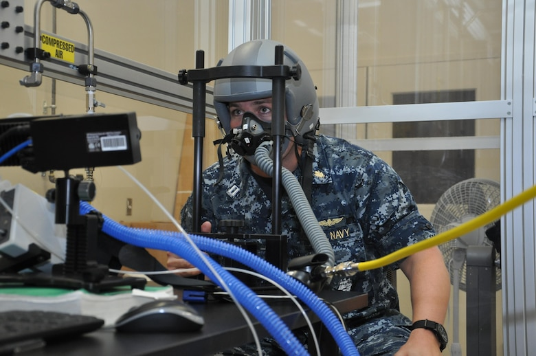 Navy Lt. Todd Seech, an aerospace experimental psychologist with the Naval Aerospace Medical Research Laboratory at Naval Medical Research Unit - Dayton, breathes through an oxygen mask in a reduced breathing environment used to examine the interaction of hypoxia and fatigue effects to determine the likelihood of mishaps. (U.S. Air Force photo/Bryan Ripple)