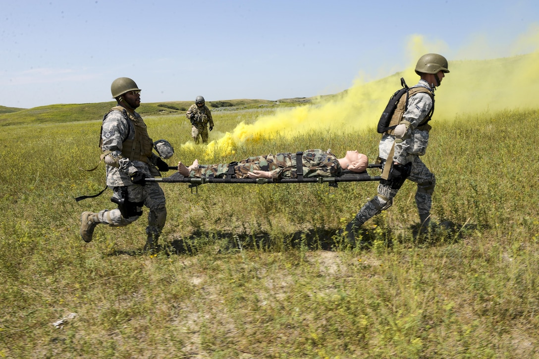 Two airmen run with a simulated battle casualty on a litter during training.
