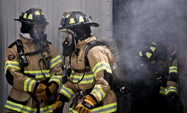 U.S. Air Force firefighters assigned to the 6th Civil Engineer Squadron exit a training building during a structural, live-burn exercise at MacDill Air Force Base, Fla., July 24, 2017. Airmen were trained on the behavior of a live fire inside a building and how to safely extinguish it. (U.S. Air Force photo by Airman 1st Class Adam R. Shanks)