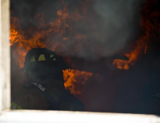 A U.S. Air Force firefighter assigned to the 6th Civil Engineer Squadron prepares to extinguish a training fire at MacDill Air Force Base, Fla., July 24, 2017. Before the flame was extinguished, firefighters were trained on a fire's behavior inside a building and the precautions they should take. (U.S. Air Force photo by Airman 1st Class Adam R. Shanks)
