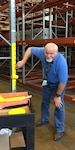 "Lawrence ""Mac"" McNinch of DLA Disposition Services at Columbus applies yellow paint to a storage rack risers in an attempt to increase their visibility."