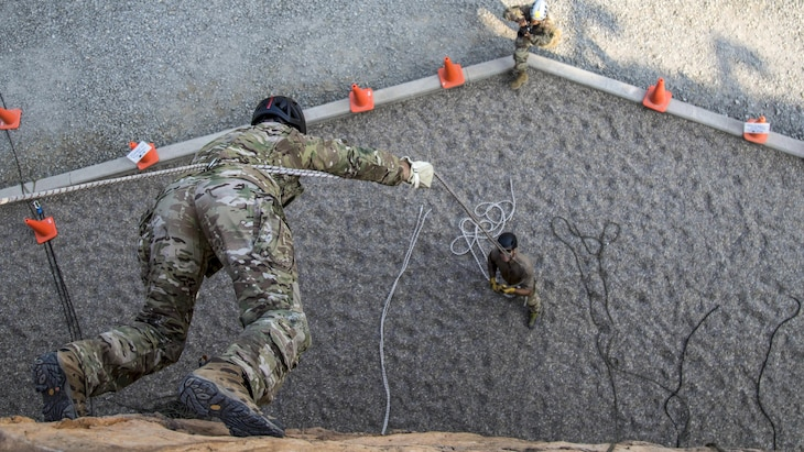 A soldier uses a rope to walk down a wall facing downward as a fellow soldier assists from the ground.