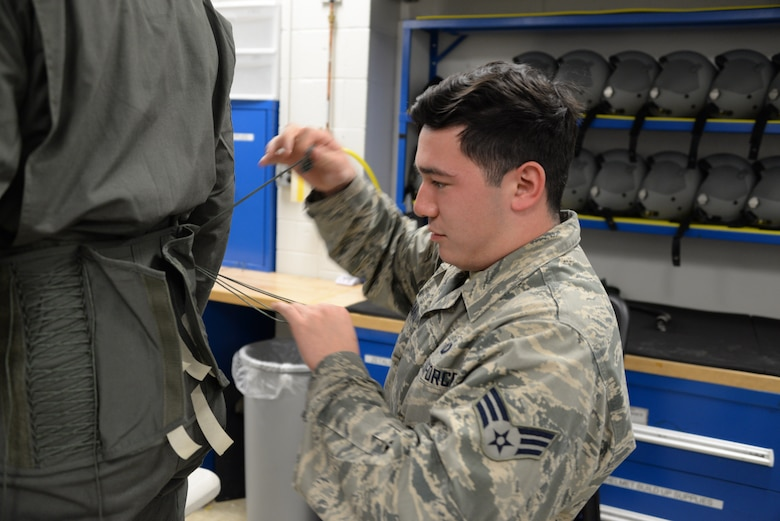 Senior Airman Carlos Garza, 80th Operations Support Squadron aircrew flight equipment technician, tightens the laces on the back of a pilots G-suit to fit there exact size. Garza hand fits each suit to the individual pilot to ensure proper fit and function. (U.S. Air Force photo by Senior Airman Robert L. McIlrath)