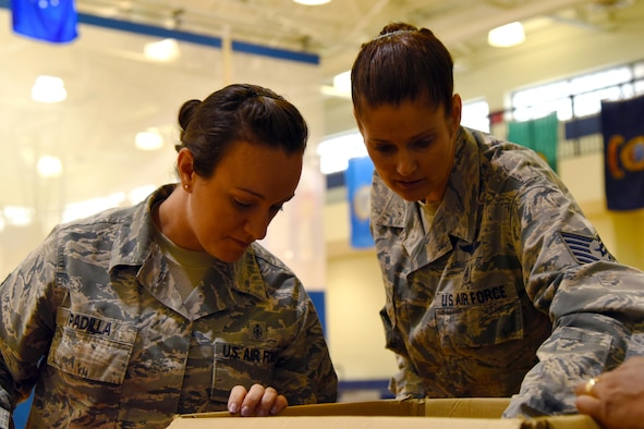 Tech. Sgt. Amanda Padilla, 23d Aerospace Medicine Squadron public health flight chief, and Tech. Sgt. Kelly Hocker, 23d Medical Operations Squadron  public health flight chief, glance in a box of school supplies during the Back the School Brigade, July 26, 2017, at Moody Air Force Base, Ga. The Back to School Brigade is used to help aid Team Moody families by making free school supplies easily available. (U.S. Air Force photo by Airman Eugene Oliver)