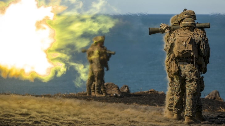 This image shows a big fireball from a weapon, as Marines fire the weapon on a beach.