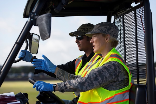From right to left. Brig. Gen. Heather Pringle, 502nd Air Base Wing and Joint Base San Antonio commander, and Jorge Ortiz, 502nd Civil Engineer Squadron Pest Management pest control technician, spread ant bait on a parade field at JBSA-Lackland, Texas, July 20, 2017. Senior leadership from 502nd ABW and JBSA accompanied the 502nd CES Pest Management pest control technicians as they completed work orders and took measures to keep the insect and animal population in check throughout the installation.