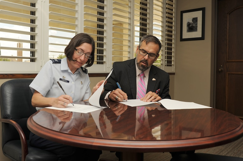 U.S. Air Force Col. Janet Urbanski, 17th Medical Group Commander, and Shane Phymell, Shannon Medical Center chief executive officer, sign a memorandum of agreement at the Shannon Medical Clinic in San Angelo, Texas, July 21, 2017. The agreement allows Goodfellow Air Force Base and Shannon medical professionals to use each other's resources, providing higher quality training environment. (U.S. Air Force photo by Senior Airman Scott Jackson/Released)