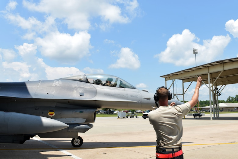 "U.S. Air Force Senior Airman John Kelly, 20th Aircraft Maintenance Squadron tactical aircraft maintainer, makes the 79th Fighter Squadron, ""Tigers,"" hand signal while marshalling out an F-16CM Fighting Falcon at Shaw Air Force Base, S.C., July 19, 2017. The 79th FS is one of three fighter squadrons under the 20th Fighter Wing which provide the suppression of enemy air defenses. (U.S. Air Force photo by Airman 1st Class Destinee Sweeney)"