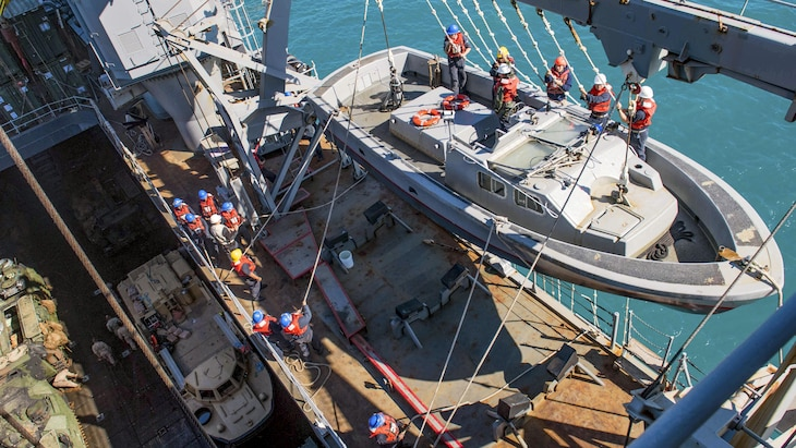 This image shows a boat suspended over a ship's deck as sailors pull ropes to bring it aboard.