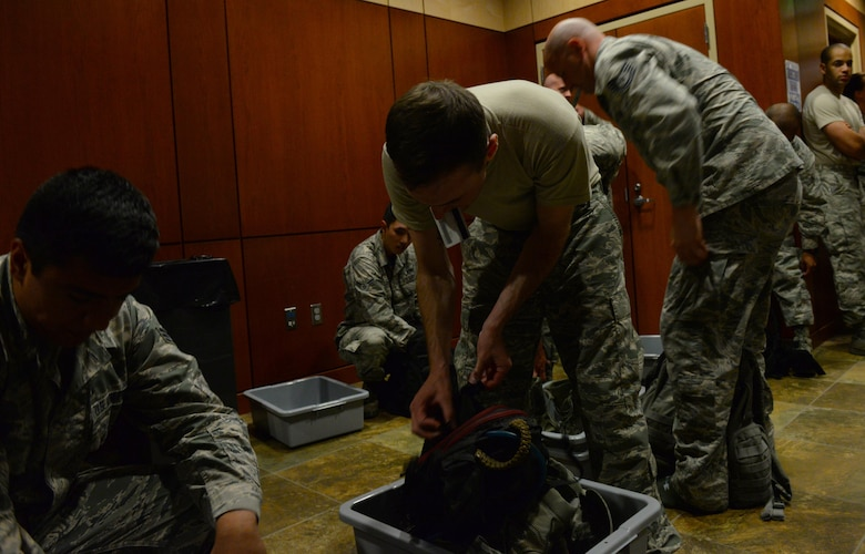 Staff Sgt. Tyler Sandberg, quality assurance assigned to the 37th Expeditionary Bomb Squadron, separates some of his carry-on luggage before processing through a sterilization room of the Deployment Center at Ellsworth Air Force Base, S.D., July 28, 2017. Ellsworth Airmen assigned to the 37th Expeditionary Bomb Squadron take the baton from the 9th Expeditionary Bomb Squadron, Dyess Air Force Base, Texas, for ongoing Continuous Bomb Presence missions occurring in U.S. Pacific Command. (U.S. Air Force photo by Airman Nicolas Z. Erwin)