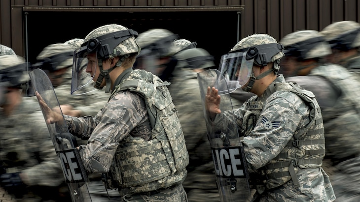 This image shows airmen in riot gear moving in formation.