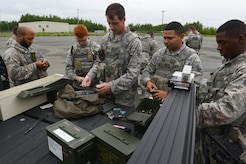 Several 673d Security Forces Squadron members load Simunition marking cartridges in preparation for active-shooter training at Joint Base Elmendorf-Richardson, Alaska, July 18, 2017. All participants were issued proper protective gear, to include a helmet, neck guard and gloves.