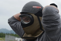 Air Force Staff Sgt. Sean Sullivan, 732nd Aircraft Maintenance Squadron crew chief, dons a protective mask in preparation for 673d Security Forces Squadron active-shooter training at Joint Base Elmendorf-Richardson, Alaska, July 18, 2017. All participants were issued proper protective gear, to include a helmet, neck guard and gloves.