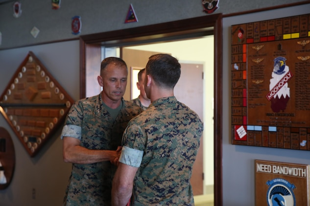 Maj. Gen. Matthew Glavy, shakes the hand of Capt. Peter Abramovs during an awards ceremony aboard Marine Corps Air Station Cherry Point, N.C., July 28, 2017. Abramovs was awarded the Air Medal for rescuing multiple Marines when his MV-22 Osprey experienced a hard landing on May 17, 2015. Abramovs was injured in the landing, but charged into the burning wreckage to help his fellow Marines. Glavy is the commanding general of 2nd Marine Aircraft Wing, and Abramovs is an AV-8B Harrier II pilot with Marine Attack Squadron 231, Marine Aircraft Group 14, 2nd MAW. (U.S. Marine Corps Photo by Pfc. Skyler Pumphret/ Released)