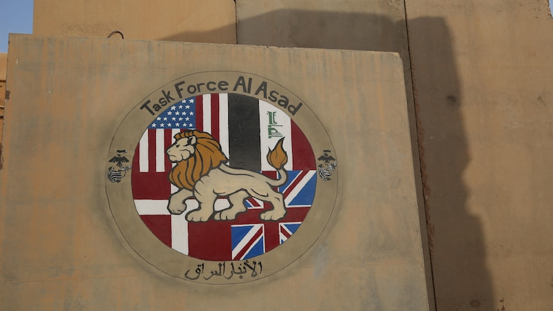 Task Force Al Asad's logo is displayed on a concrete barrier in front of the Task Force Headquarters at Al Asad Air Base, Iraq, July 8, 2017. The Task Force, in its fourth iteration, was stood up in 2015 and comprises of coalition forces including the U.S., British, and Danish Armies. Task Force Al Asad's mission is to advise and assist and build partner capacity with the Iraqi Security Forces in Al Anbar province in support of Combined Joint Task Force-Operation Inherent Resolve, the global coalition to defeat ISIS in Iraq and Syria. (U.S. Marine Corps photo by 1st Lt. Dave Williams)