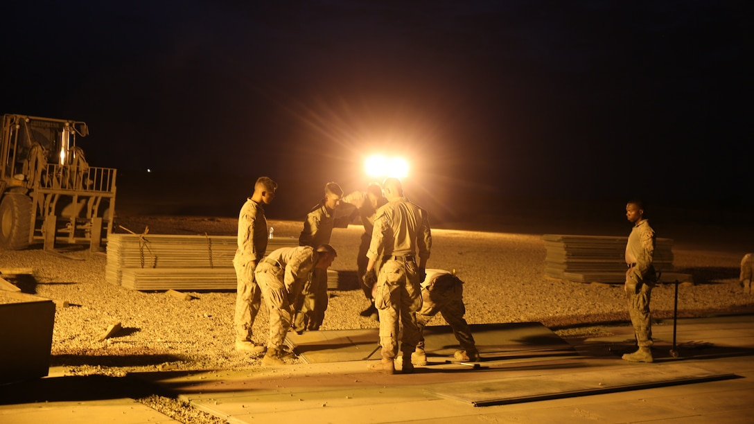 U.S. Marines attached to Task Force Al Asad with Marine Wing Support Squadron (MWSS) 372, Special Purpose Marine Air-Ground Task Force-Crisis Response-Central Command, lay expeditionary airfield matting in support of engineering operations at Al Asad Air Base, Iraq, July 7, 2017. The Marines of the Engineering Detachment work daily on a variety of engineer tasks in support of the master base plan for Task Force Al Asad. Task Force Al Asad's mission is to advise and assist  and build partner capacity with the Iraqi Security Forces in Al Anbar province in support of Combined Joint Task Force-Operation Inherent Resolve, the global coalition to defeat ISIS in Iraq and Syria. (U.S. Marine Corps photo by 1st Lt. Dave Williams)