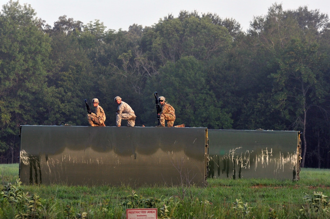 Three U.S. Army Soldiers from a Multi-Role Bridge Company kneel on top of an Improved Ribbon Bridge (IRB) Bay Section waiting to hook it up to a CH-47 Chinook of Company B, 7th (General Support Aviation) Battalion, 158th Aviation Regiment, 244th Aviation Brigade, Army Reserve Aviation Command during River Assault 2017 on Fort Chaffee Manuever Training Center, July 26, 2017. The Chinook dropped off the bay in the Arkansas River in order for the IRB to be built across the river, the culminating event of River Assault. Operation River Assault is one of the key training events that demonstrates that America's Army Reserve is the most capable, combat ready, and lethal Federal Reserve Force in the history of the nation. (U.S. Army Reserve Photo by Sgt. 1st Class Clinton Wood)