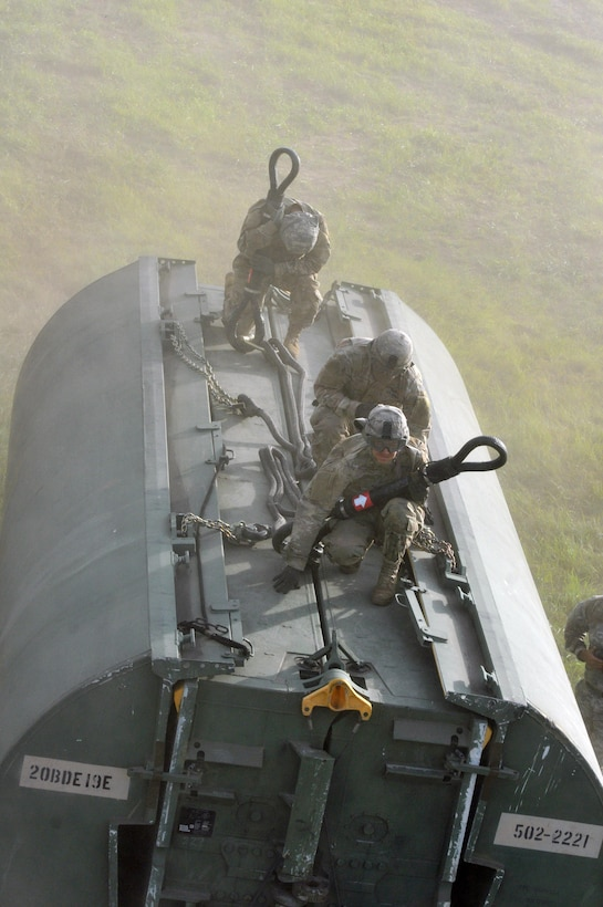 Three U.S. Army Soldiers from a Multi-Role Bridge Company kneel on top of an Improved Ribbon Bridge (IRB) Bay Section waiting to hook it up to a a CH-47 Chinook of Company B, 7th (General Support Aviation) Battalion, 158th Aviation Regiment, 244th Aviation Brigade, Army Reserve Aviation Command during River Assault 2017 on Fort Chaffee Manuever Training Center, July 26, 2017. The Chinook dropped off the bay in the Arkansas River in order for the IRB to be built across the river, the culminating event of River Assault. Operation River Assault is one of the key training events that demonstrates that America's Army Reserve is the most capable, combat ready, and lethal Federal Reserve Force in the history of the nation. (U.S. Army Reserve Photo by Sgt. 1st Class Clinton Wood)